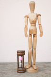Wood mannequin and hourglass to spending time Royalty Free Stock Photo