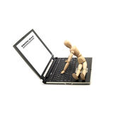 Wood mannequin and laptop. Wood mannequin sitting on a laptop isolated on white background Royalty Free Stock Image