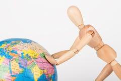 Wood mannequin push a world globe Stock Photo