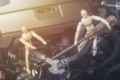 Wood Mannequin are Repairing the engine With intent and sun-lighting. stock image