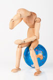 Wood mannequin sitting on top of a globe Royalty Free Stock Photos