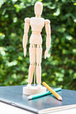 Wood mannequin standing on artist work paperbook Royalty Free Stock Photos