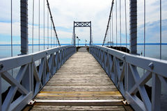 Wood and metal bridge perspective. Perspective view cable and wood bridge of a small coastal town Stock Photos
