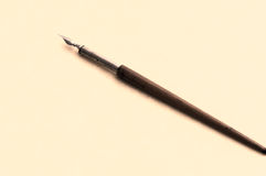 Wood and metal pen. Old fashioned ink dip pen for writing or drawing on parchment paper background Stock Photography
