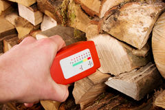 Wood moisture meter. Hand with a wood moisture meter in front of a stack of firewood Stock Photography