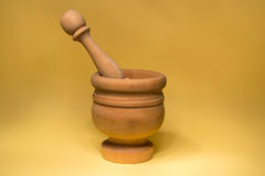 Wood mortar. Antique wood mortar on yellow background Stock Photography