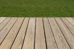 Wood deck and grass background. Wood with natural pattern deck and grass in daylight background royalty free stock image