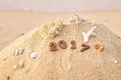 Wood nummer 2017 på strandbakgrundsidé Arkivfoton