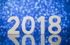 Wood nummerreflexion för nytt år 2018 på den glass tabellen över blåa lodisar royaltyfri fotografi