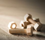 Wood nut and bolt on wood table work concept. Royalty Free Stock Image