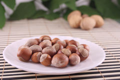 Wood Nuts In A Plate Removed Against Walnuts