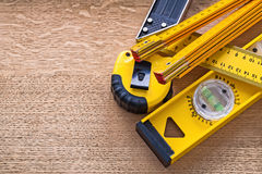 Wood oaken board with yellow objects of. Measurement construction concept Stock Photography