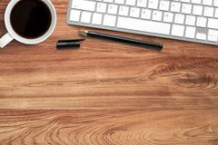 Wood office desk table with computer keyboard, coffee cup and pen. Top view with copy space, flat lay.  royalty free stock photography