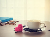 Wood office table with cup of latte coffee and pink heart shape. Sign on blurry white drape texture background, view from front wood table Stock Photo