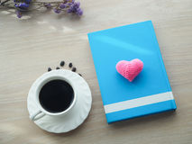 Wood office table with hot black coffee cup, dried purple flower. And pink heart shape sign on blank blue cover book. view from front office table Royalty Free Stock Image