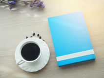 Wood office table with hot black coffee cup, dries purple flower Stock Image