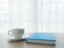Wood office table with white coffee cup and blue notebook paper Stock Image
