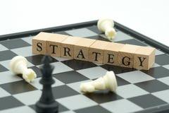 Wood ord som förläggas på schackbrädet med ett schackstycke på baksidaNen Royaltyfri Foto