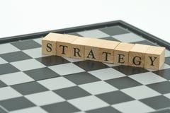 Wood ordstrategi som förläggas på schackbrädet med ett schackstycke på th Royaltyfri Foto