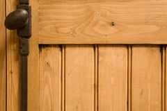 Wood paneling. Detail of wooden panelled furniture with iron handle Stock Photos