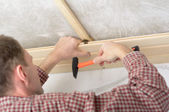 Wood panelling the ceiling. Contractor installing wood panels on a ceiling Royalty Free Stock Photo