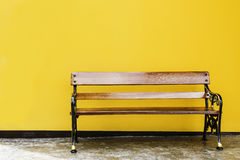 Wood park bench in front of yellow wall. Stock Photos