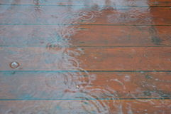 Wood patio flooded by rain. Patio flooded by rain and water drops. Wood terrace flooded by rain. Outdoor. Rainy day Stock Photos