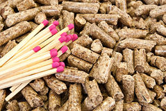 Wood pellets. Solid background of yellow wooden pellets and some pink-head matches stock photo