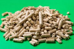 Wood pellets on a green background , copy space. Biofuels. stock image