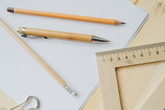 Wood pencil, pen, triangle, briefpapier clip on the desk in daylight. Office table Royalty Free Stock Photos