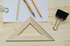 Wood pencil, pen, triangle, briefpapier clip on the desk in daylight. Office table Royalty Free Stock Image