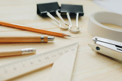 Wood pencil, pen, triangle, briefpapier clips, hefter on the desk in daylight. Office table Royalty Free Stock Photo