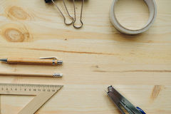 Wood pencil, pen, triangle, briefpapier clips, hefter on the desk in daylight. Office table Royalty Free Stock Photos