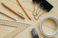 Wood pencil, pen, triangle, briefpapier clips, hefter on the desk in daylight. Office table Stock Image