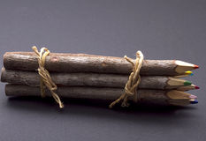 Wood Pencils on gray. Colored pencils/crayons made of wood and tied in a bundle with rope, isolated on a gray background royalty free stock images
