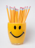 Wood pencils in smiley cup. Wooden pencils stacked in a smiley pencil holder Royalty Free Stock Photos