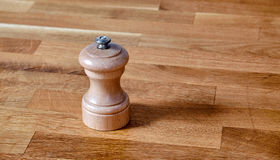 Wood pepper mill on a taule Stock Photos