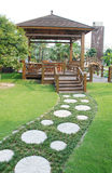Wood pergola and stone way. The wood pergola and stone stepping stone pavement in a tropical holiday resort garden Royalty Free Stock Image