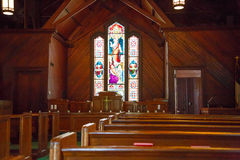 Wood Pews and Stained Glass in Small Church Royalty Free Stock Images