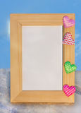 Wood photo frame with multi-colored hearts. Photo frame with valentines on on snow royalty free stock photography