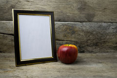 Wood photo frame and red apple on wooden table Royalty Free Stock Images