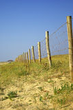 Wood picket barrier in french dunes. Wood post barrier foreground to background on dunes with little vegetation and a totally blue sky royalty free stock photo