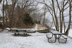 Wood picnic tables with trail and snow along Potomac river royalty free stock photos