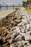 Wood Pier Beyond Rock Seawall Stock Images