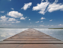Wood pier in large lake under blue sky Stock Photography