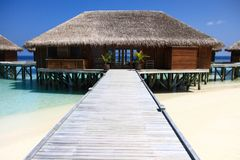 Wood Pier Leading to Overwater Bungalows on Pacific Ocean in the. Maldives stock photo