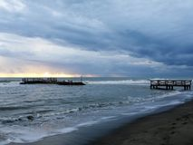Wood pier under storm clouds, Ostia, Rome. Storm clouds at sunset on the rough sea during autumn, Lido di Ostia, Rome, Italy Royalty Free Stock Images