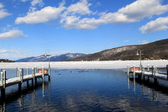 Wood piers on the melting waters of pretty lake Stock Photography