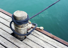 Wood pile with coiled rope on the dock. On a summer day Stock Photos