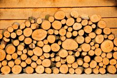 Wood Pile And Porch. Pile of chopped tree logs to be used as fire wood stacked neatly on decked porch area Royalty Free Stock Photo